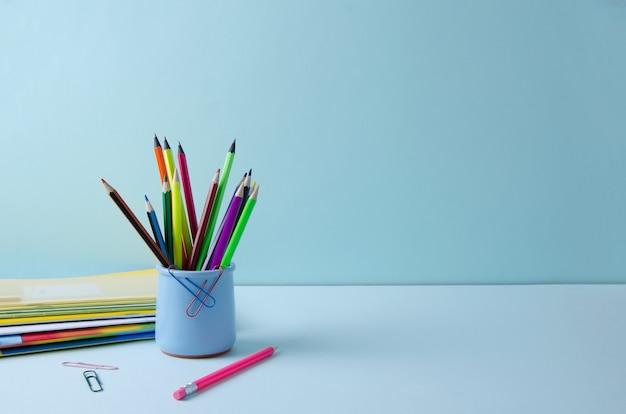 Veelkleurige potloden in een blauwe standaard op een blauwe achtergrond.