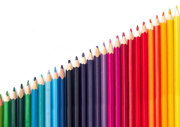 Veelkleurige potloden in een rij op kleurtemperatuur op een witte achtergrond isoleren, plat leggen
