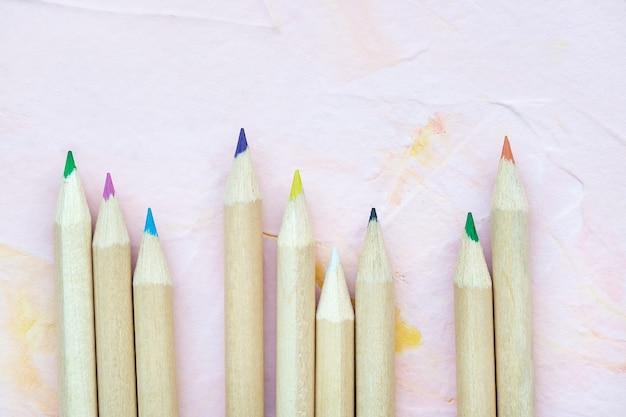 Veelkleurige potloden op roze achtergrond