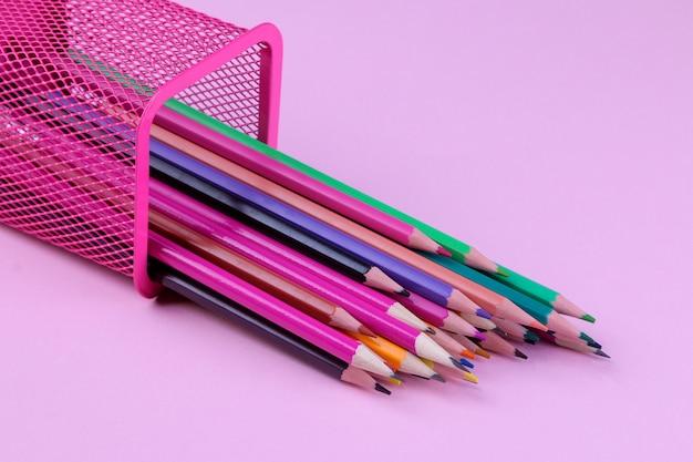 Veelkleurige potloden vallen uit het glas op een felroze achtergrond.