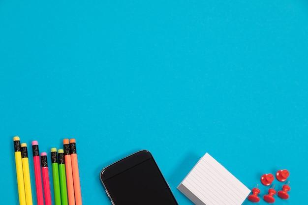 Veelkleurige potloden, zwarte mobiele telefoon, een stapel wit kladpapier en een groep rode pushpins zijn half zichtbaar liggend op een lichtblauw oppervlak geïsoleerd