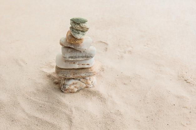 Veelkleurige rivierkiezelstenen liggen willekeurig op het zand naast de zee