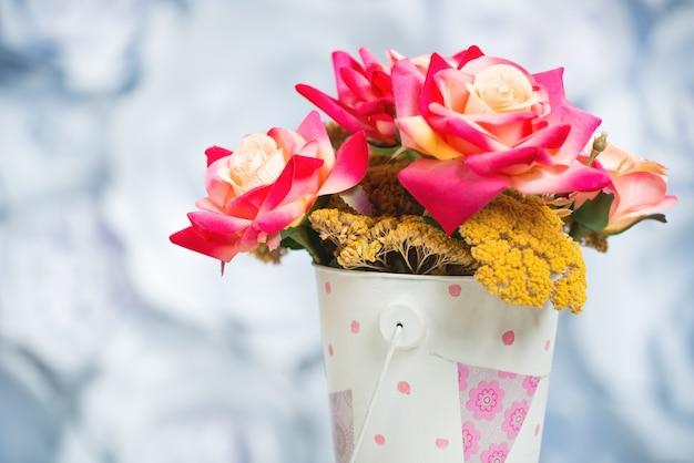Veelkleurige rozen en droogbloemen in een licht emmertje met een roze print