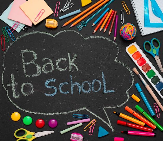 Veelkleurige schoolbenodigdheden, potloden en een getekende wolk met kopieerruimte voor tekst.