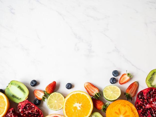 Veelkleurige seizoensgebonden gezonde natuurlijke fruitgrens met persimmon, bosbessen, sinaasappel, kiwi, aardbeien, grapefruit, granaatappel, stukjes sinaasappel.