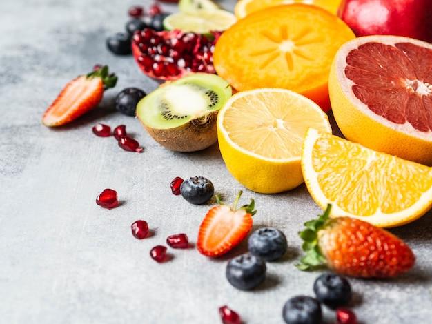 Veelkleurige seizoensgebonden gezonde natuurlijke fruitsamenstelling met persimmon, bosbessen, sinaasappel, kiwi, aardbeien, grapefruit, granaatappel, stukjes sinaasappel. kopieer ruimte