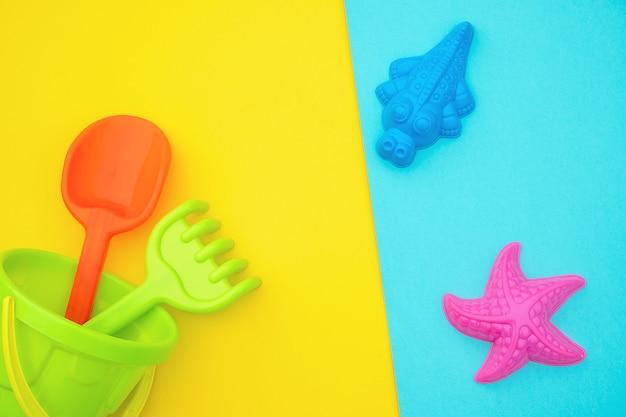 Veelkleurige set kinderspeelgoed voor zomerspelen in zandbak of op zandstrand op blauwe gele achtergrond