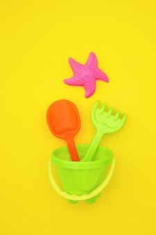 Veelkleurige set kinderspeelgoed voor zomerspelen in zandbak of op zandstrand op gele achtergrond.