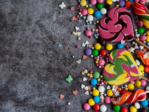 Veelkleurige snoepjes, dragees en lollies op een zwarte ondergrond