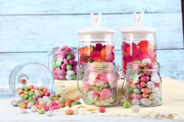Veelkleurige snoepjes in glazen potten op een houten achtergrond kleur