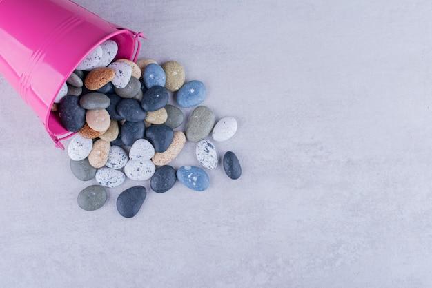 Veelkleurige strandstenen in een schaal op betonnen ondergrond