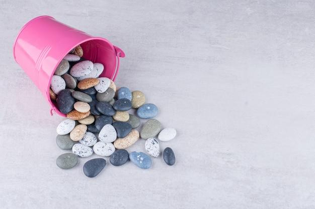 Veelkleurige strandstenen voor knutselen op een betonnen ondergrond