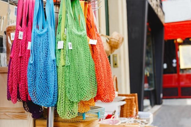 Veelkleurige string tassen in de winkel. geen plastic, zero waste concept store. recyclebare boodschappentassen voor hergebruik