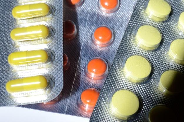 Veelkleurige tabletten in blisterverpakkingen liggen op een lichte achtergrond. detailopname.
