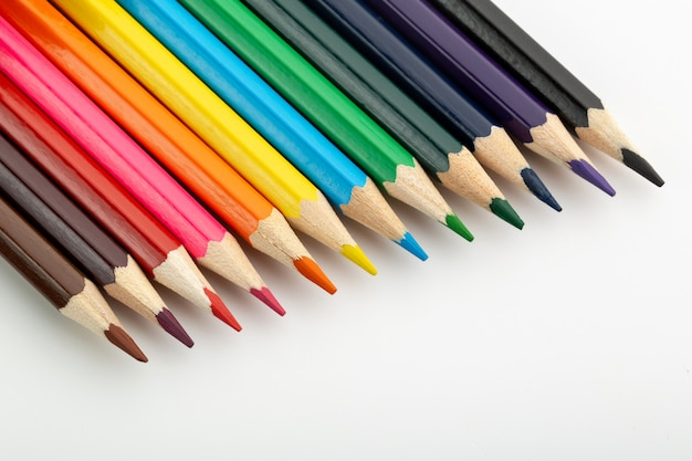 Veelkleurige tekenpotloden bekleed helder op wit bureau