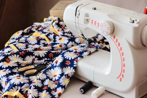Veelkleurige textiel- en kleermakersschaar lag op het paneel van de naaimachine