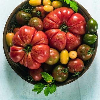 Veelkleurige tomaten van verschillende kleuren, vormen en maten in een kleiplaat op tafel. zomer achtergrond