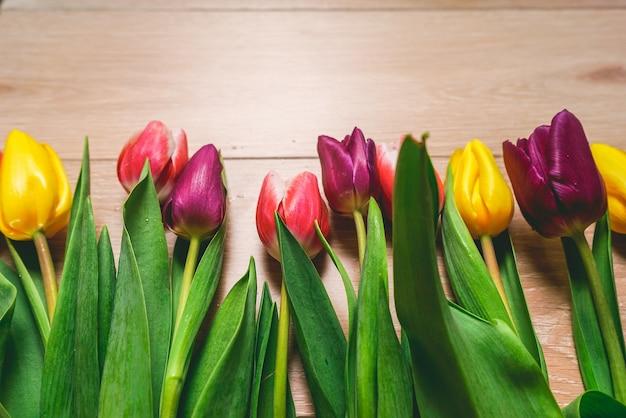 Veelkleurige tulpen op tafel, een boeket bloemen als cadeau voor een vrouw