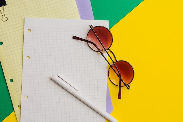 Veelkleurige vellen papier op een gekleurde achtergrond en pen office kladblok clip bril