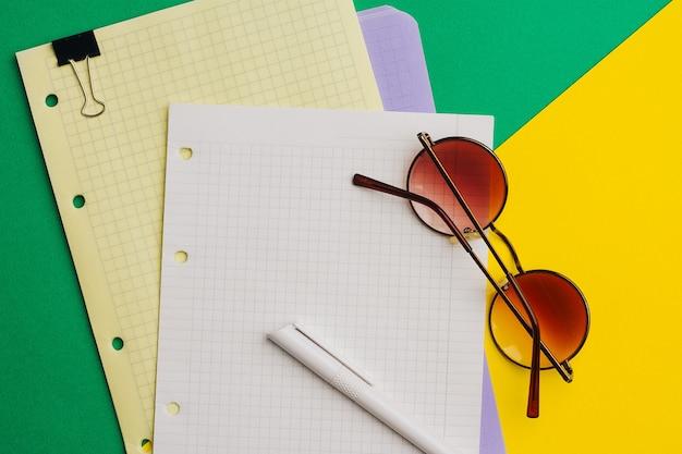Veelkleurige vellen papier op gekleurd en pen kantoor kladblok clip bril.