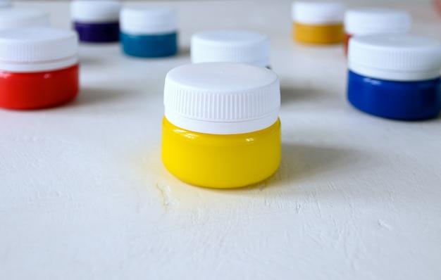 Veelkleurige verf in potten met een wit deksel op een witte tafel close-up selectieve aandacht