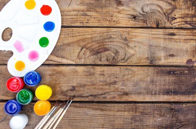Veelkleurige verf, penselenpalet, penseel, liggen op een houten achtergrond bovenaanzicht