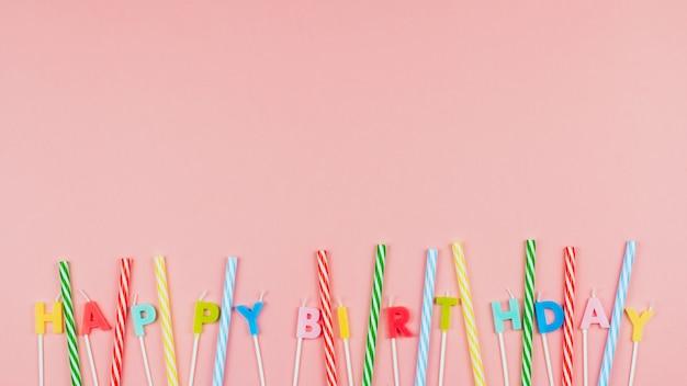 Veelkleurige verjaardagskaarsen en gestreepte rietjes voor een cocktail