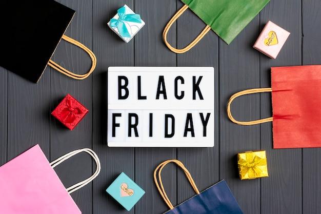 Veelkleurige verpakkingstassen, geschenkdozen lightbox met tekst black friday op donkergrijs oppervlak plat leggen