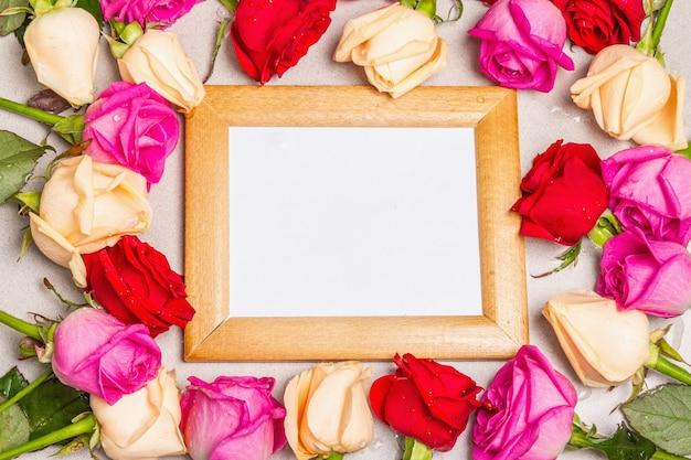 Veelkleurige verse rozen en een houten frame op lichte stenen achtergrond. feestelijk cadeau, wenskaart voor pasen, verjaardag, valentijnsdag of bruiloft. vakantieconcept, een plek voor tekst
