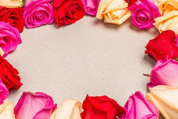 Veelkleurige verse rozen in de vorm van een frame op lichte stenen achtergrond. feestelijk cadeau, wenskaart voor pasen, verjaardag, valentijnsdag of bruiloft. vakantieconcept, een plek voor tekst