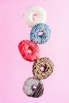Veelkleurige versierde donuts in beweging vallen