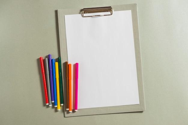 Veelkleurige viltstiften en klembord met blanco papier
