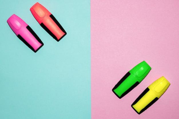 Veelkleurige viltstiften op pastelkleurroze en pastelkleur blauwe achtergrond. kleurrijke markeringen