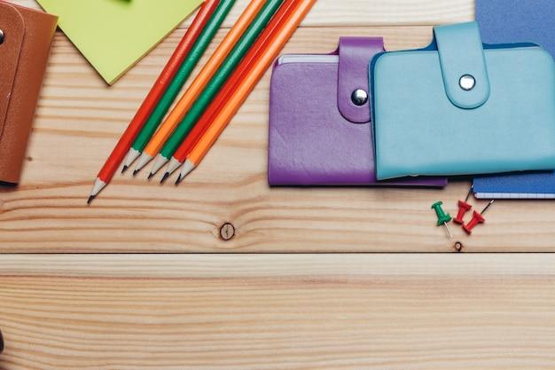 Veelkleurige visitekaartjeshouders potloden blocnotes school objecten bovenaanzicht. hoge kwaliteit foto