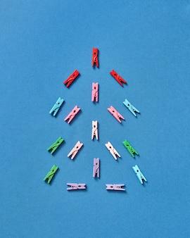 Veelkleurige wasknijpers in de vorm van een kerstboom op een blauw met kopie ruimte. bovenaanzicht.