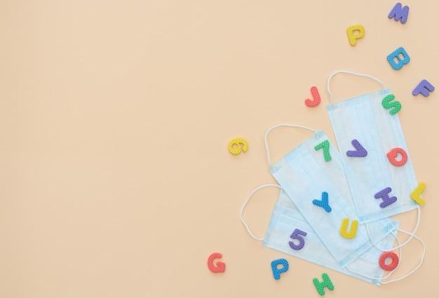 Veelkleurige zachte engelse letters en cijfers liggen op gele medische gezichtsmaskers