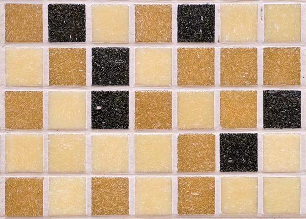 Veelkleurige zwart oranje bruine en gele vierkante ruwe matte mozaïektegels, naadloos patroon voor decoratie. naadloze eindeloze mozaïek tegel achtergrond voor badkamer of keukenschort