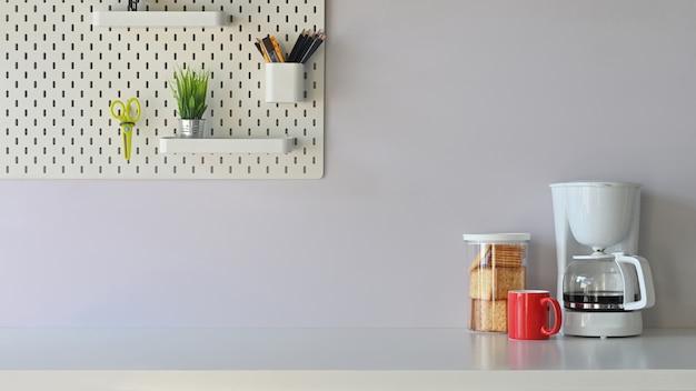 Veelzijdige tafel in de ochtendvibe inclusief koffiezetapparaat, koffiekopje, koekjes staat op tafel potplant, potloodhouder en schaar op de witte plank.