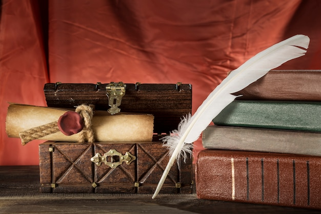 Veer in de buurt van verzegelde rol in oude kist en vintage boeken