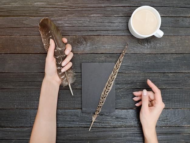 Veer in een vrouwelijke hand, een notitieboekje en een kopje koffie. oude houten tafel. bovenaanzicht