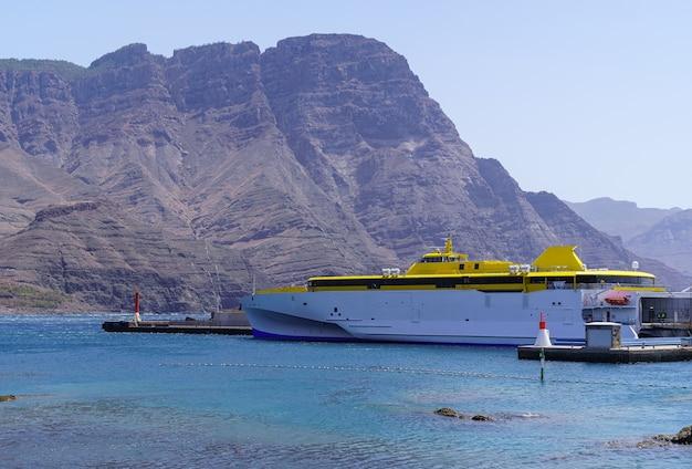 Veerboot aangemeerd in de haven naast een enorme berg aan zee, het landschap van gran canaria. europa,
