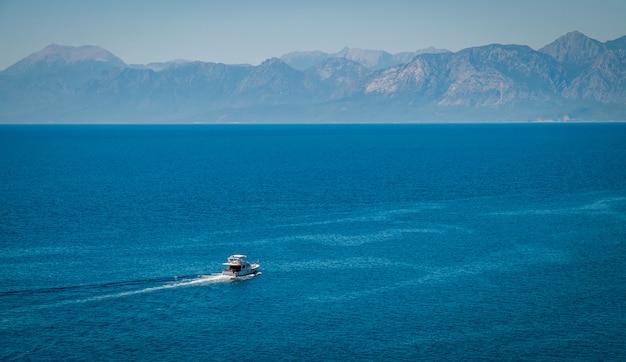 Veerboot op blauwe zee en bergachtergrond - het mooie oriëntatiepunt van de het landschapsreis van turkije