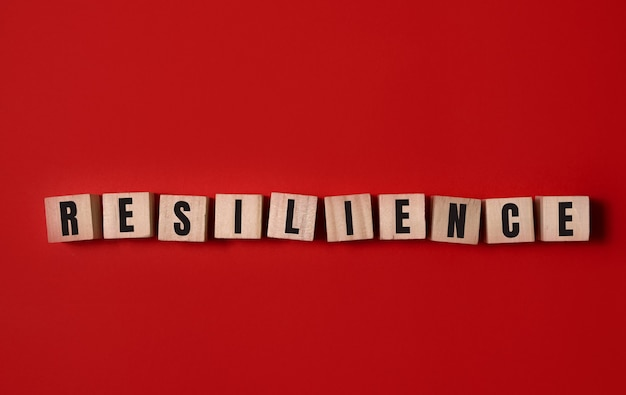 Veerkracht symbool. houten kubussen met woord 'veerkracht'. mooie rode achtergrond. bedrijfs- en veerkrachtconcept. kopieer ruimte.
