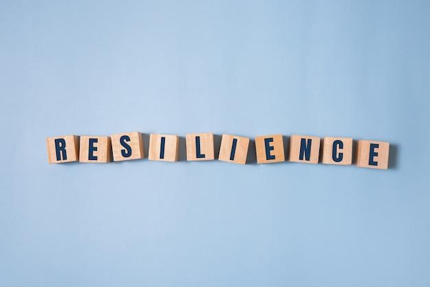 Veerkracht woord concept op kubussen op blauwe achtergrond.