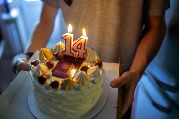 Veertienjarige jongen met zijn verjaardagstaart versierd met paspoortschuimgebakjescrème