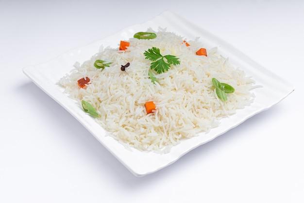 Veg pulao gemaakt met basmatirijst, groenten en kruiden gerangschikt in een vierkant wit servies