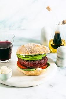 Vegan burger zonder vlees met avocado, tomaten en spinazie op tafel en rode wijn in een glas