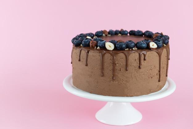 Vegan chocoladetaart met bosbessen en hazelnoten op een roze achtergrond