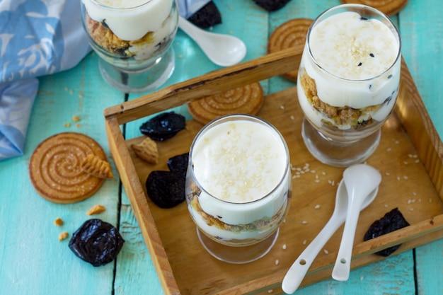 Vegan dessert met slagroom noten havermout pruimen en sesam in glazen glaasjes