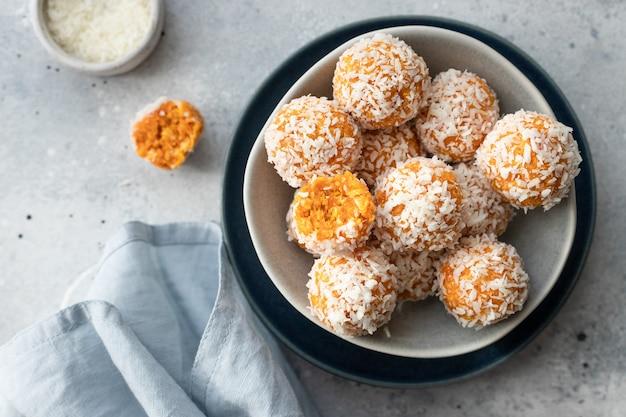 Vegan energie-geluksballen met gedroogde abrikozen en kokos in blauwe kom rauw veganistisch dessert